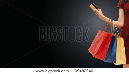 people, sale, black friday and consumerism concept - close up of woman with shopping bags and bank or credit card