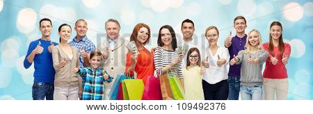 gesture, sale, shopping and people concept - group of smiling men, women and kids showing thumbs up and holding shopping bags with money over blue holidays lights background