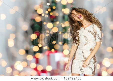 people, holidays, party and fashion concept - happy young woman or teen girl in fancy dress with sequins and long wavy hair dancing over christmas tree lights background