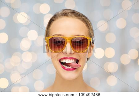 people, expression, joy and fashion concept - smiling young woman in sunglasses with pink lipstick on lips showing tongue over holidays lights background