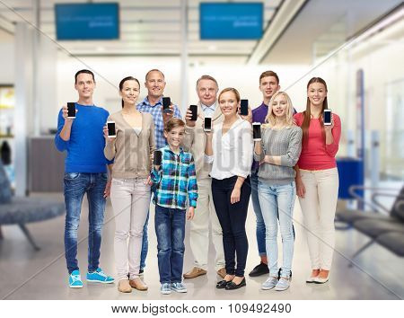 family, technology, travel and tourism concept - group of smiling people with smartphones over airport waiting room background