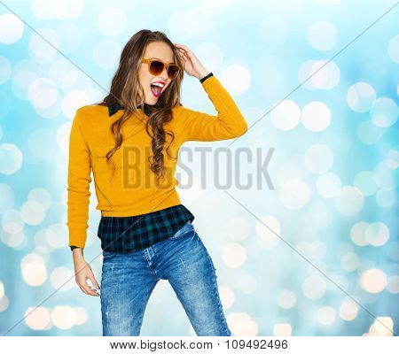 people, style and fashion concept - happy young woman or teen girl in casual clothes and sunglasses having fun over blue holidays lights background