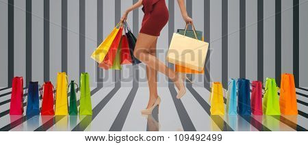 people, sale and consumerism concept - close up of woman in red short skirt and high heeled shoes with shopping bags over gray striped 3d background