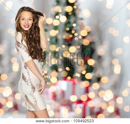 people, holidays, hairstyle and fashion concept - happy young woman or teen girl in fancy dress with sequins touching long wavy hair over christmas tree lights background