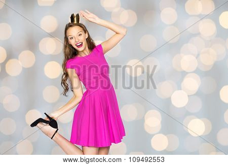 people, holidays and fashion concept - happy young woman or teen girl in pink dress and princess crown over lights background