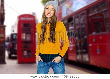 people, travel, tourism, style and fashion concept - happy young woman or teen girl in casual clothes and hipster hat over london city street background