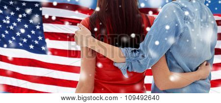 people, homosexuality, same-sex marriage, gay and love concept - close up of happy women couple hugging over american flag background over snow effect