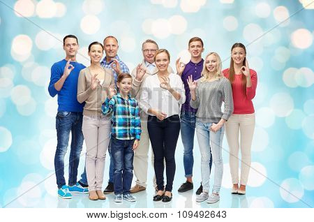gesture, family, generation and people concept - group of smiling men, women and boy showing ok hand sign over blue holidays lights background