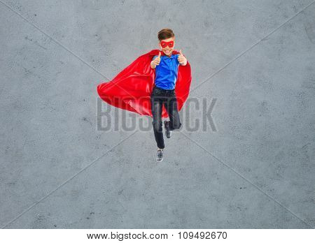 happiness, freedom, childhood, movement and people concept - boy in red super hero cape and mask flying in air and showing thumbs up over gray concrete background