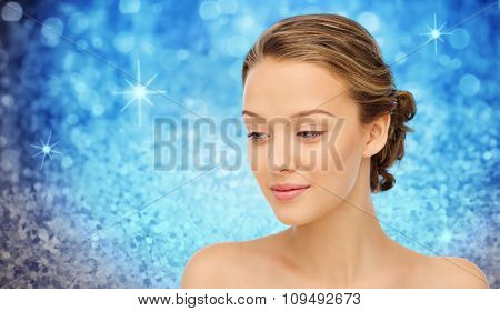 beauty, people and health concept - smiling young woman face and shoulders over blue holidays lights or glitter background
