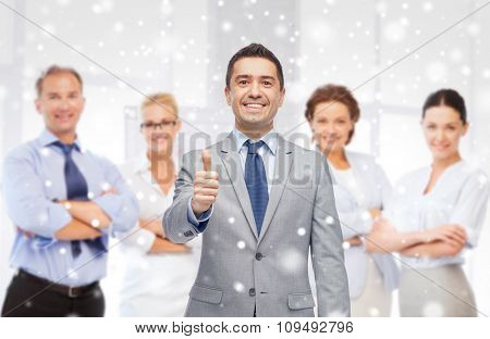 business, people, gesture and office concept - happy businessman with team showing thumbs up over office background and snow effect