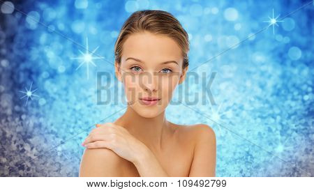 beauty, people, body care and health concept - smiling young woman face and hand on bare shoulder over blue holidays lights or glitter background
