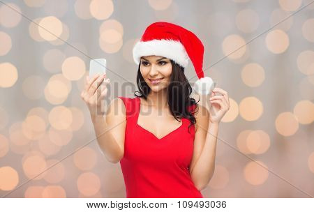 people, holidays, christmas and technology concept - beautiful sexy woman in red santa hat taking selfie picture by smartphone over holidays lights background