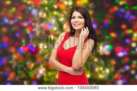 people, holidays and fashion concept - beautiful sexy woman in red dress over christmas lights background