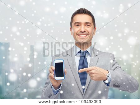 business, people and technology concept - happy smiling businessman in suit showing smartphone black blank screen over city background and snow effect