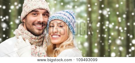 winter, fashion, couple, christmas and people concept - smiling man and woman in hats and scarf hugging over snow and forest background