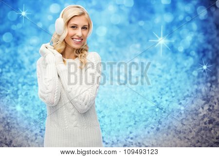 winter, fashion, christmas and people concept - smiling young woman in earmuffs and sweater over blue glitter or holidays lights background