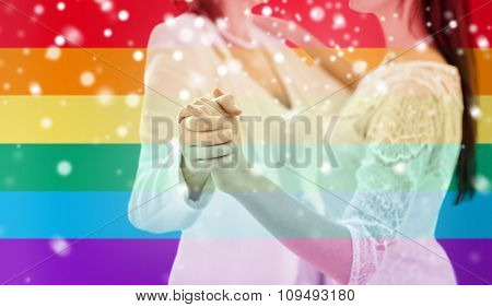 people, homosexuality, same-sex marriage and love concept - close up of happy married lesbian couple dancing over rainbow flag stripes background over snow effect