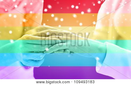 people, homosexuality, same-sex marriage and love concept - close up of happy lesbian couple hands putting on wedding ring over rainbow flag stripes background over snow effect
