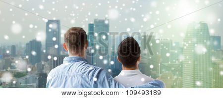 people, homosexuality, same-sex marriage, gay and love concept - close up of happy male gay couple or friends hugging from back over city background and snow effect