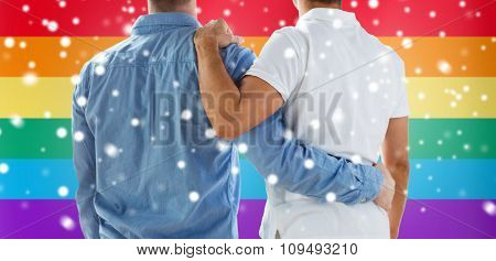 people, homosexuality, same-sex marriage, gay and love concept - close up of happy male gay couple or friends hugging from back over rainbow flag background and snow effect