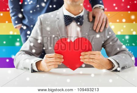 people, homosexuality, same-sex marriage, valentines day and love concept - close up of happy married male gay couple with red paper heart shape on wedding over rainbow flag background and snow effect