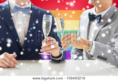 people, celebration, homosexuality, same-sex marriage and love concept - close up of happy married male gay couple drinking sparkling wine on wedding over rainbow flag background and snow effect