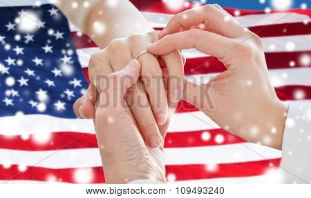 people, homosexuality, same-sex marriage and love concept - close up of happy lesbian couple hands putting on wedding ring over american flag background over snow effect