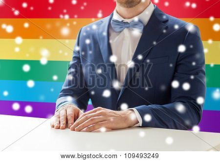people, gay, wedding and same-sex marriage concept - close up of best man or groom in suit and bow-tie at table over rainbow flag background and snow effect