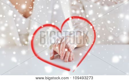 people, homosexuality, same-sex marriage and love concept - close up of happy married lesbian couple hands over snow effect