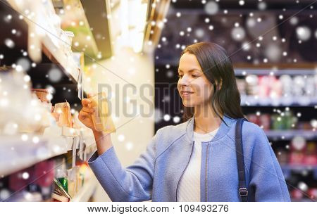 sale, shopping, consumerism and people concept - happy young woman choosing and buying food in market over snow effect