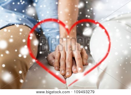 people, homosexuality, same-sex marriage, valentines day and love concept - close up of happy male gay couple holding hands with red heart shape and snow effect