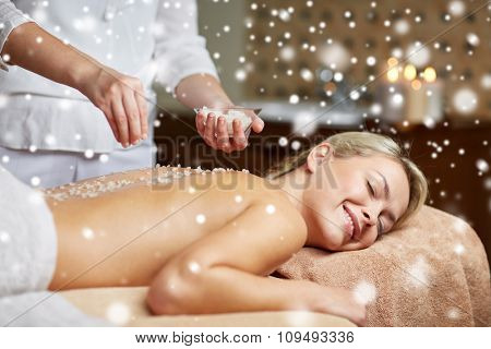people, beauty, spa, massage and relaxation concept - close up of beautiful young woman lying with closed eyes and therapist applying sea salt to back in spa with snow effect