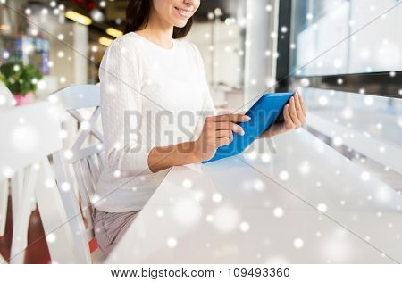 people, technology and lifestyle concept - close up of smiling woman with tablet pc computer at cafe over snow effect