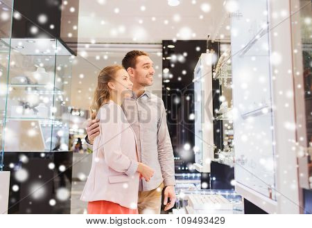 sale, consumerism and people concept - happy couple looking at shopping window in jewelry store in mall with snow effect