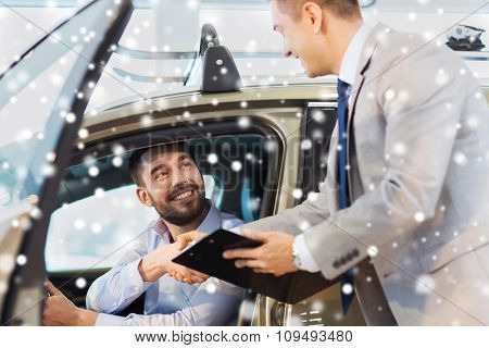 auto business, car sale, consumerism, gesture and people concept - happy man with car dealer making deal and shaking hands in auto show or salon over snow effect