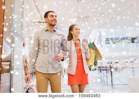 sale, consumerism and people concept - happy young couple with shopping bags walking in mall with snow effect