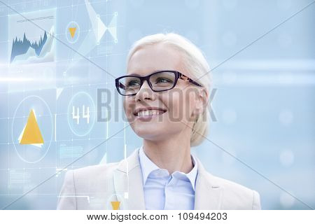 business, people, development and future technology concept - young smiling businesswoman in eyeglasses with virtual screen and charts projection outdoors