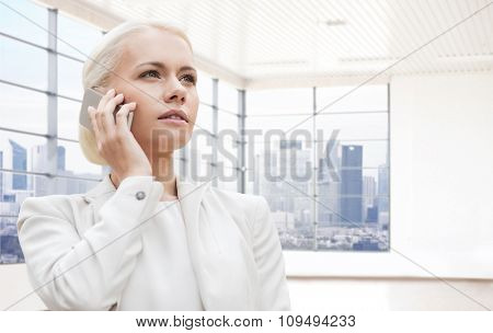 business, technology and people concept - businesswoman calling on smartphone over office room or new apartment background