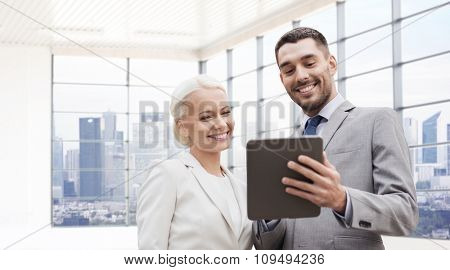 business, partnership, technology and people concept - smiling businessman and businesswoman with tablet pc computer over office room or new apartment background