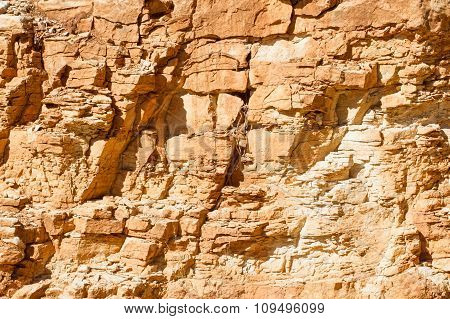 Background stone texture.  Yellow rock wall at sunset light