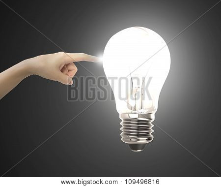 Human Index Finger Touching Lightbulb With Bright Light