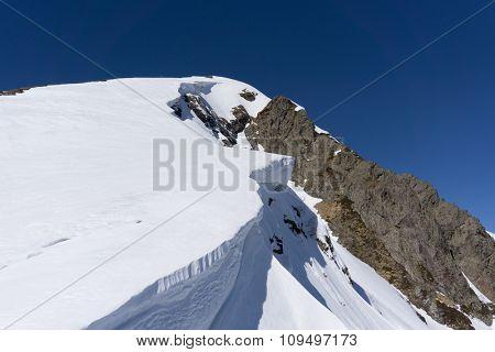 Winter snowy mountain peak and blue sky