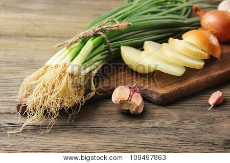 Fresh different onions with garlic on board against wooden background