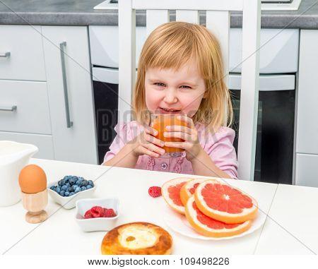 little child drinking juice for breakfast