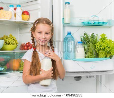 little girl holding a bottle of milk near opened fridge