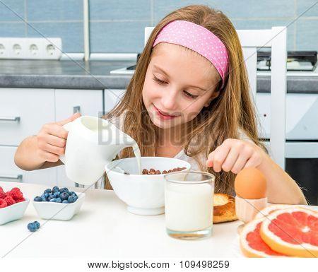 little girl eating chocolate balls for breakfast