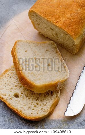 Sliced loaf of homemade  bread on cooking paper