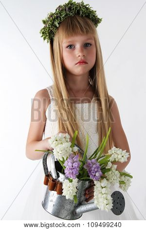 the charming little girl in a white dress poses in the camera with a watering can in hands