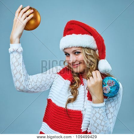 Girl dressed in santa hat holding a Christmas decoration